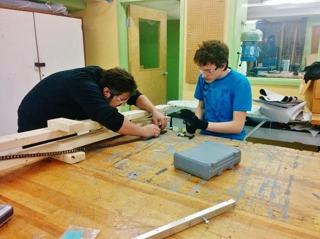 David, mentor en mécanique et un étudiant travaillent sur le prototype du robot - Photo courtoisie