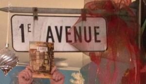 La couverture du roman 1re avenue et signalisation 1e avenue du restaurant Chez Madame Charlotte.