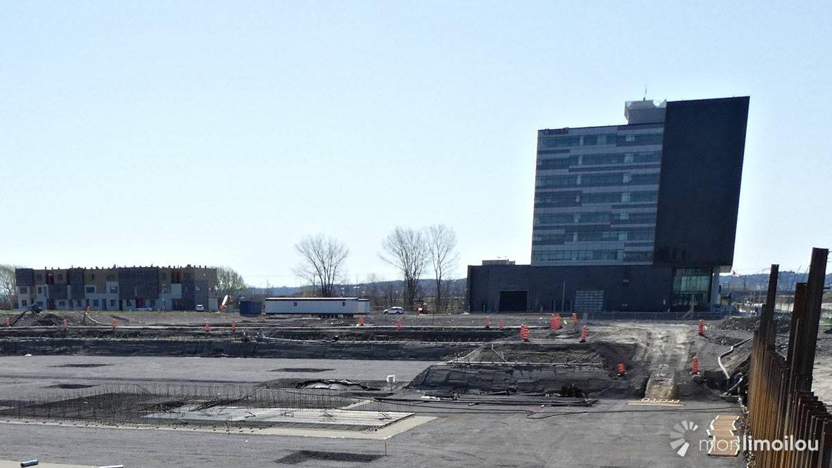 À gauche, direction est, les maisons en rangée de BTL Immobiliers. À droite, l'édifice du fédéral. Au premier plan, l'immeuble en construction du CNESST.